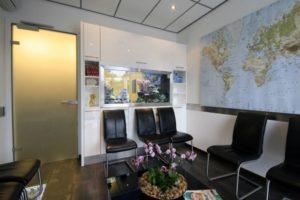 de wachtkamer met een wereldkaart en een zoutwater aquarium